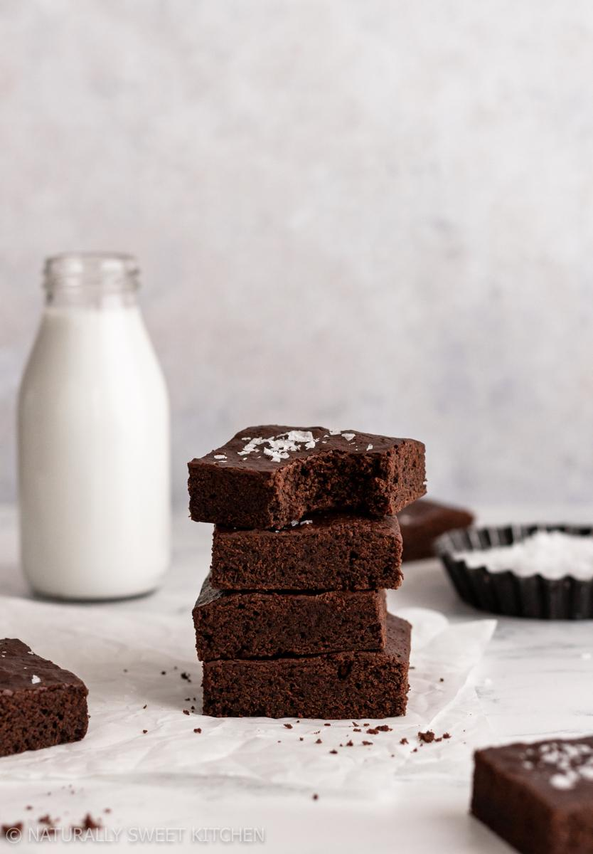 a stack of naturally sweetened brownies on some white wax paper in front of a full milk bottle
