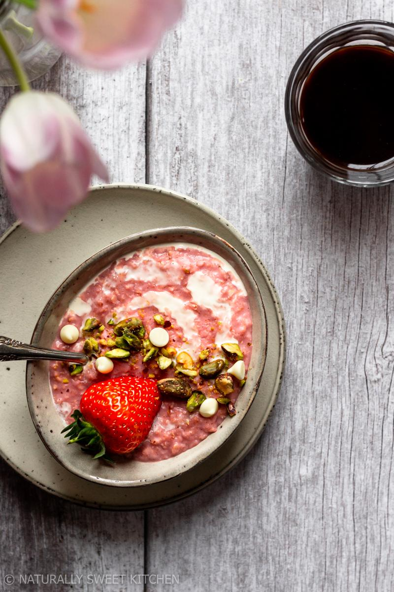 an aerial shot of a bowl of strawberry oatmeal on a wooden table with an espresso and flower vase on the side