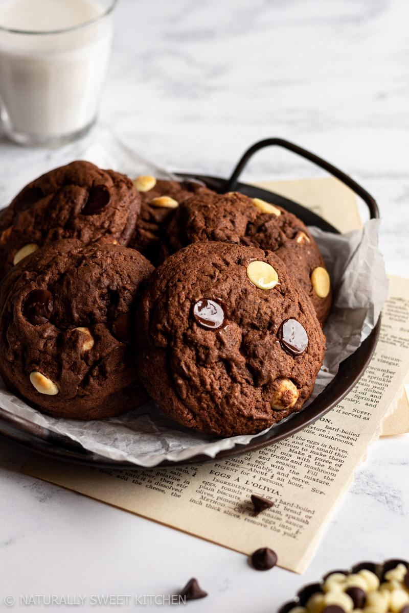a handled serving tray holds a bunch of triple chocolate cookies and there is a glass of milk in the background and a plate of chocolate chips in the foreground