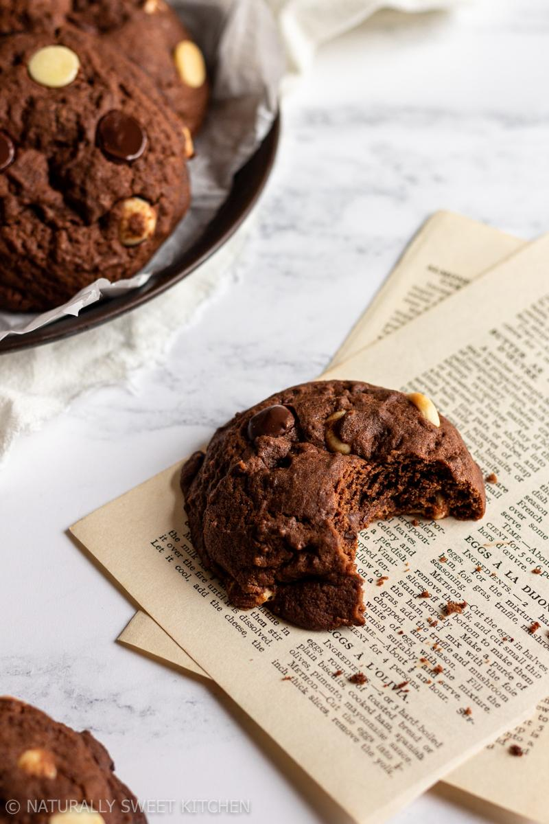 a triple chocolate cookie has a bite missing and sits on a set of vintage cookbook pages with a tray of cookies in the background