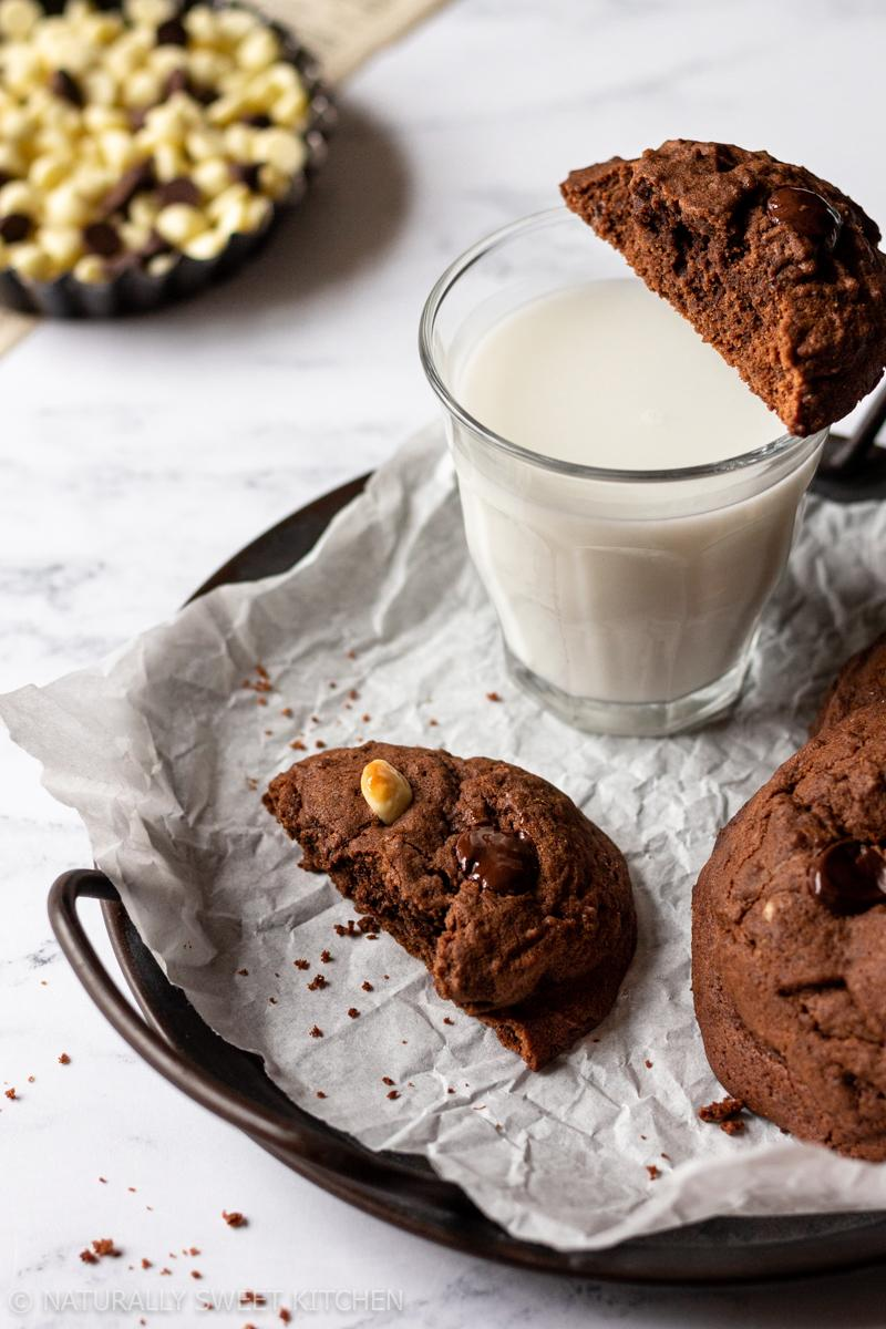 a serving tray carries a few triple chocolate cookies and a glass of milk that is topped with a half a cookie