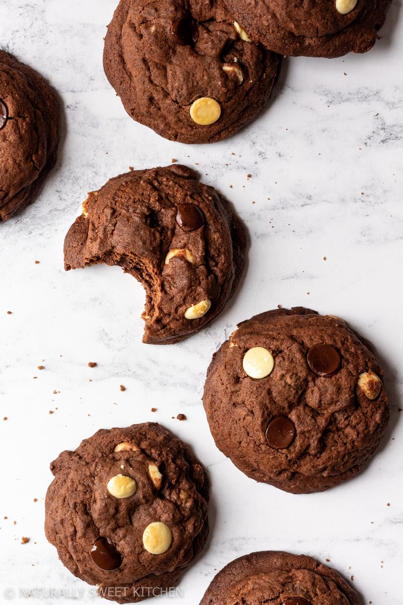 an aerial shot of a bunch of triple chocolate cookies on a marble table top with scattered crumbs