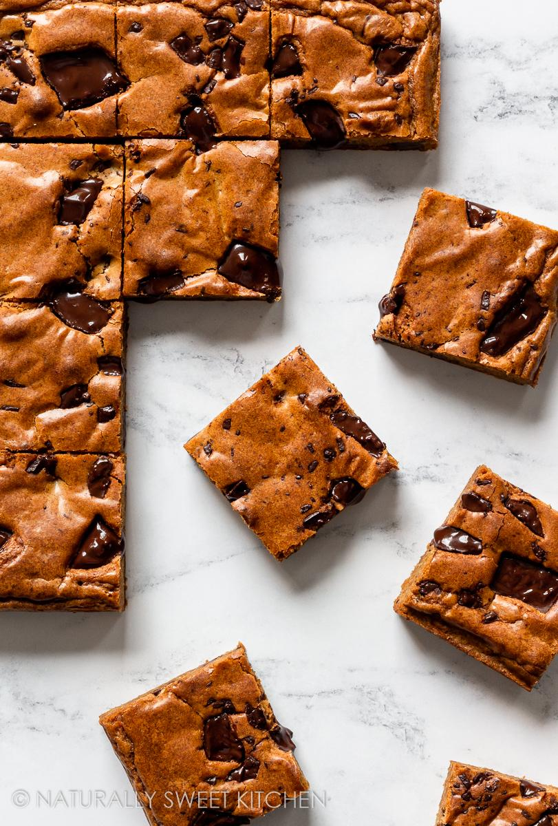 bars of a blondie recipe set with dark chocolate chunks scattered around a marble countertop