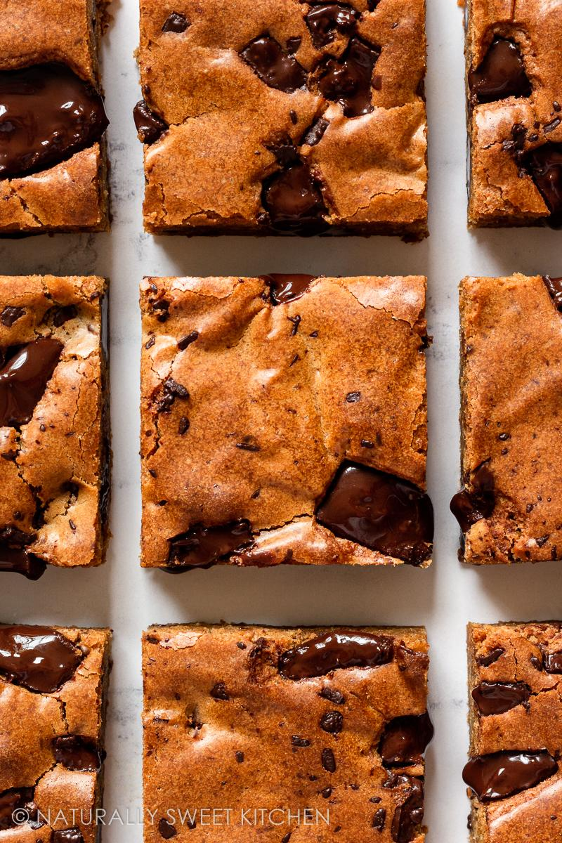 nine blondies lined up in rows of three with melty dark chocolate chunks studded on top