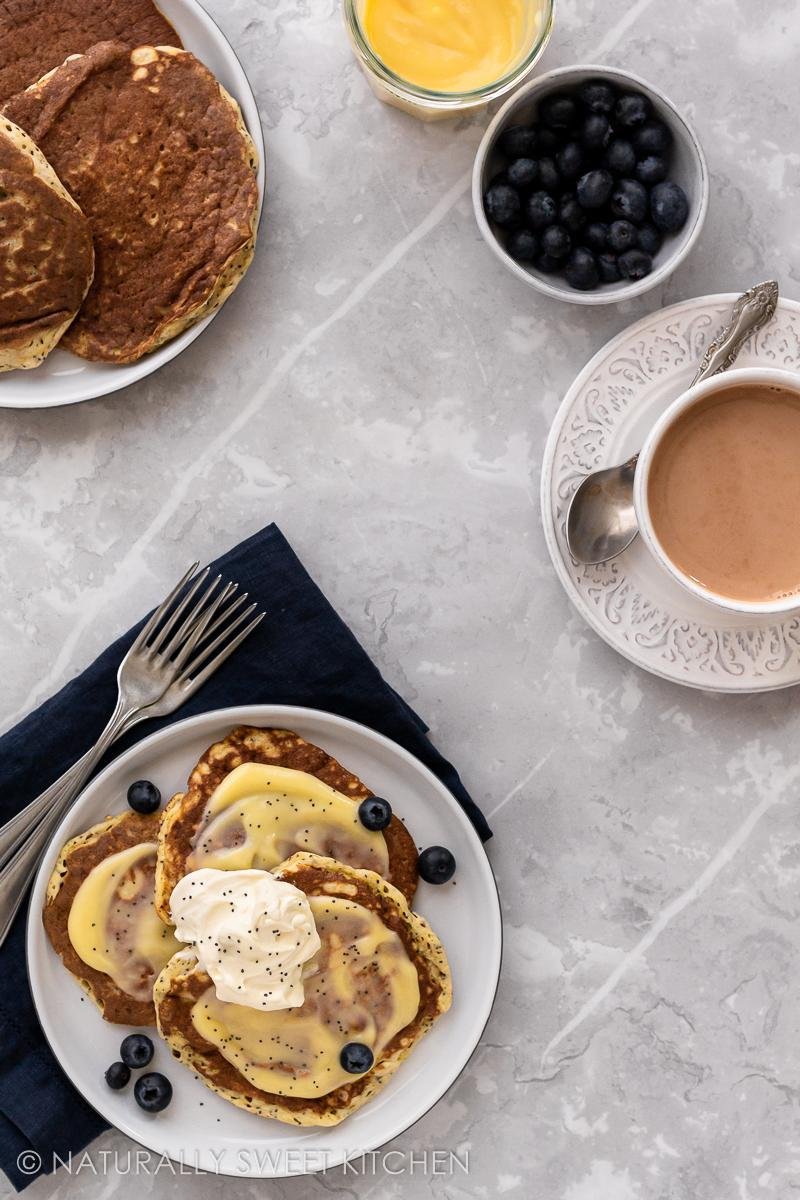 an aerial view of a marble table set with a platter of lemon pancakes, cup of tea, bowl of blueberries, and lemon curd
