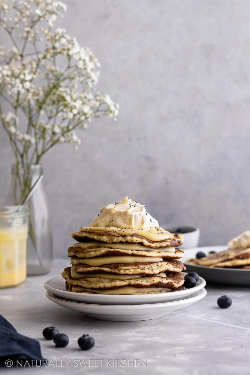 a tablescape displaying a stack of lemon poppyseed pancakes topped with whipped cream, lemon curd and blueberries with a vase of white flowers in the background
