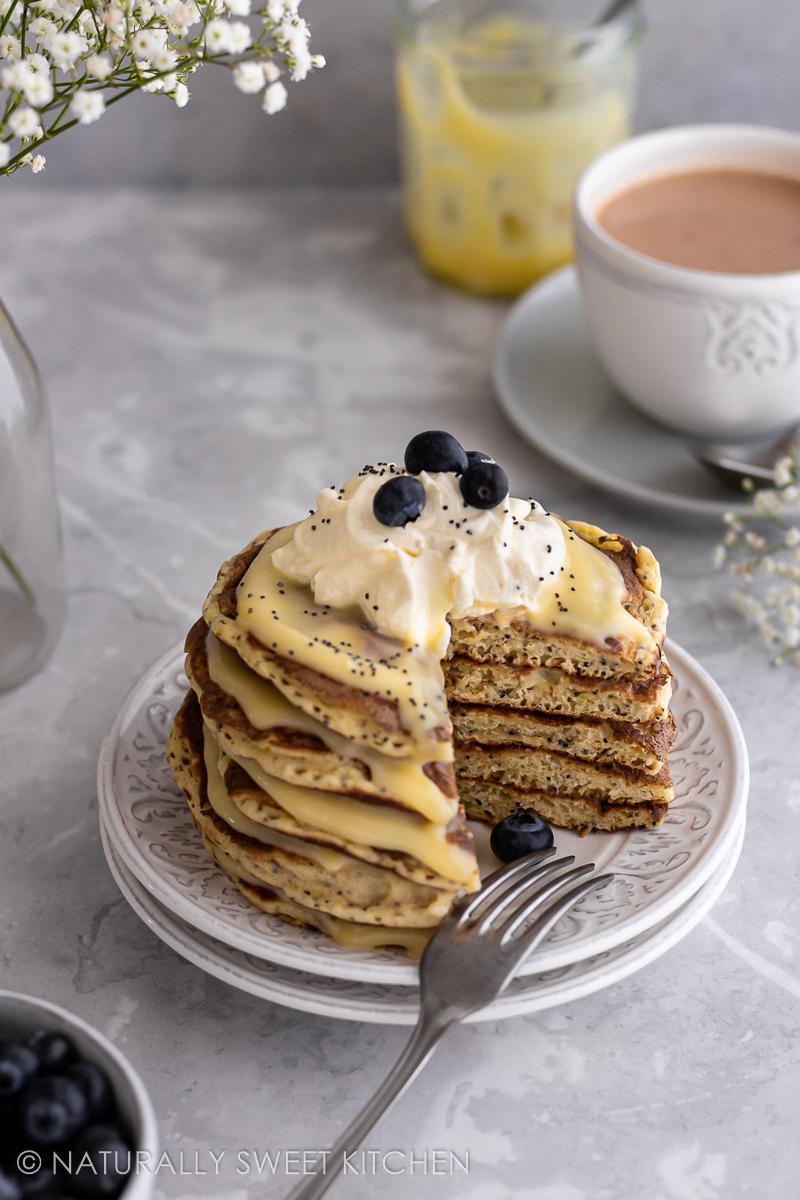 a cross-cut of a stack of lemon poppyseed pancakes layered with lemon curd with a cup of tea in the background