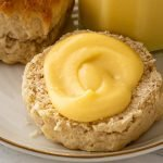 a scone on an ivory plate topped with a swirl of refined sugar free lemon curd