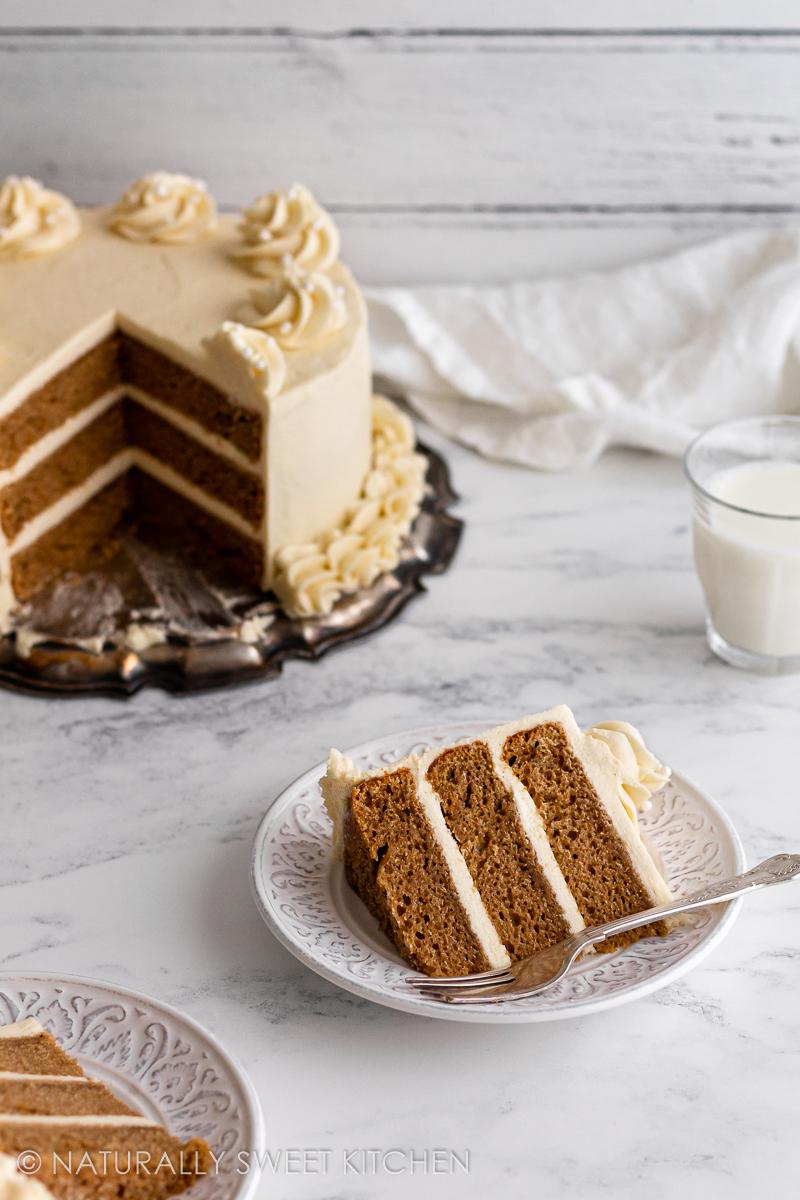 two slices of refined sugar free vanilla cake on plates next to the full cake with pieces missing.
