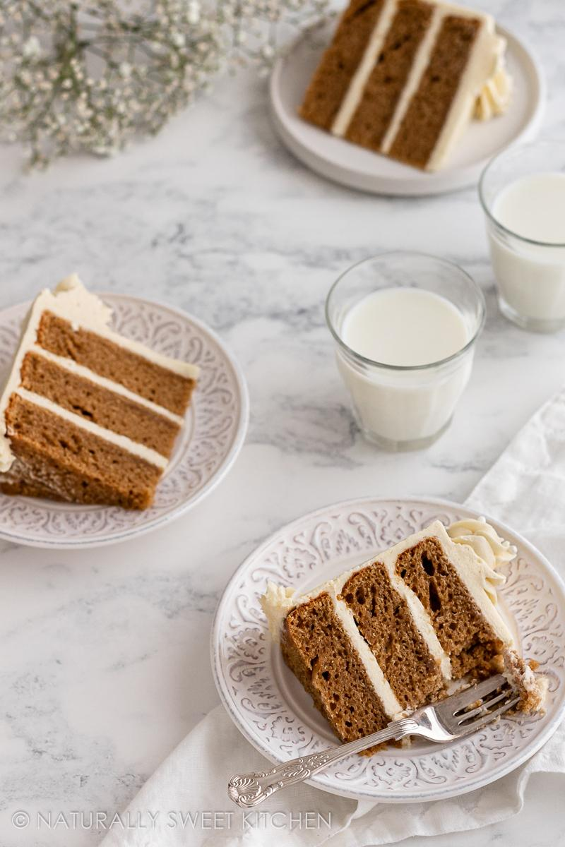 three plates of the best vanilla cake recipe on a marble table with two glasses of milk between them