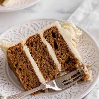 a slice of refined sugar free vanilla cake on a white plate with a fork taking a piece out of the corner