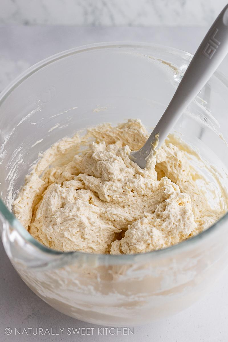 a bowl of fluffy vanilla buttercream frosting with a white spatula sticking out of it