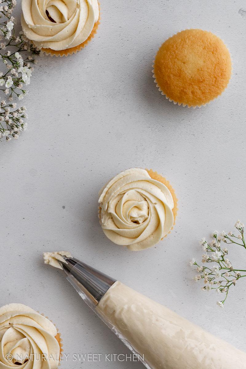 an aerial shot of 4 yellow cupcakes topped with vanilla frosting with a piping bag near the bottom of the image
