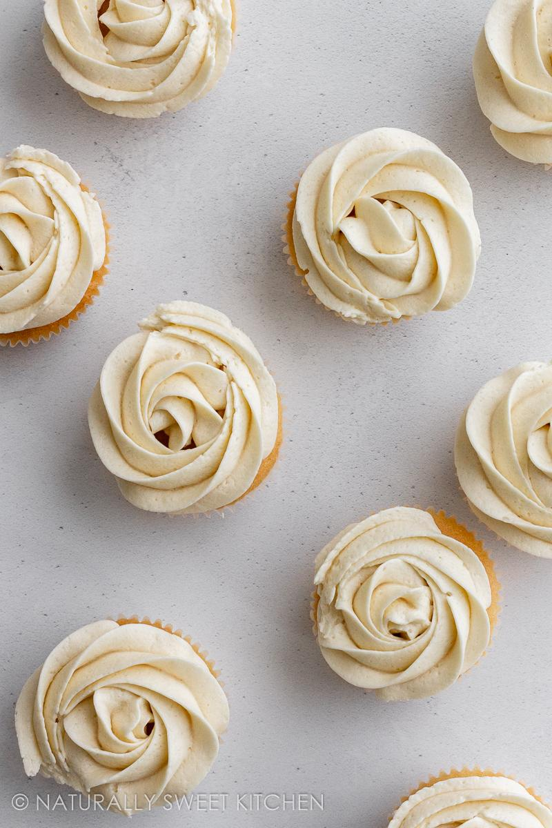 a bunch of vanilla cupcakes topped with swirls of vanilla buttercream frosting