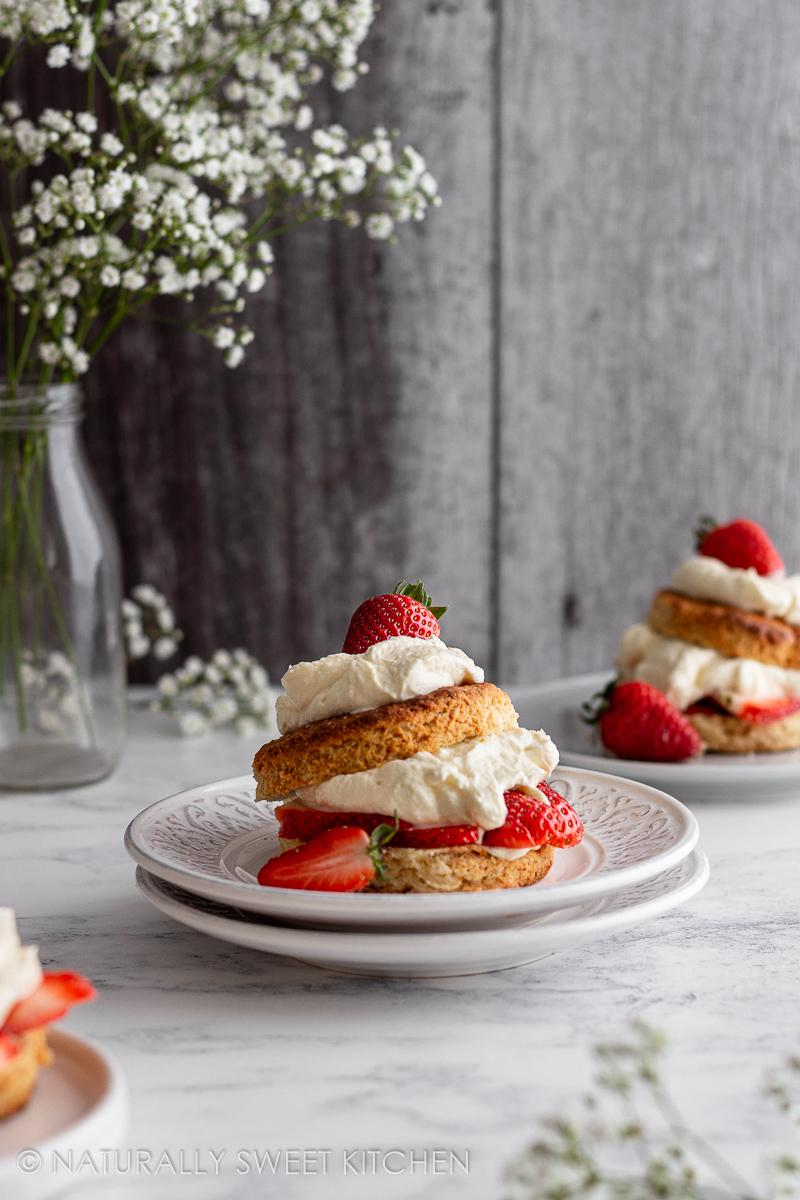 three servings of refined sugar free strawberry shortcake on a marble countertop with a vase of white flowers in the backgrounnd