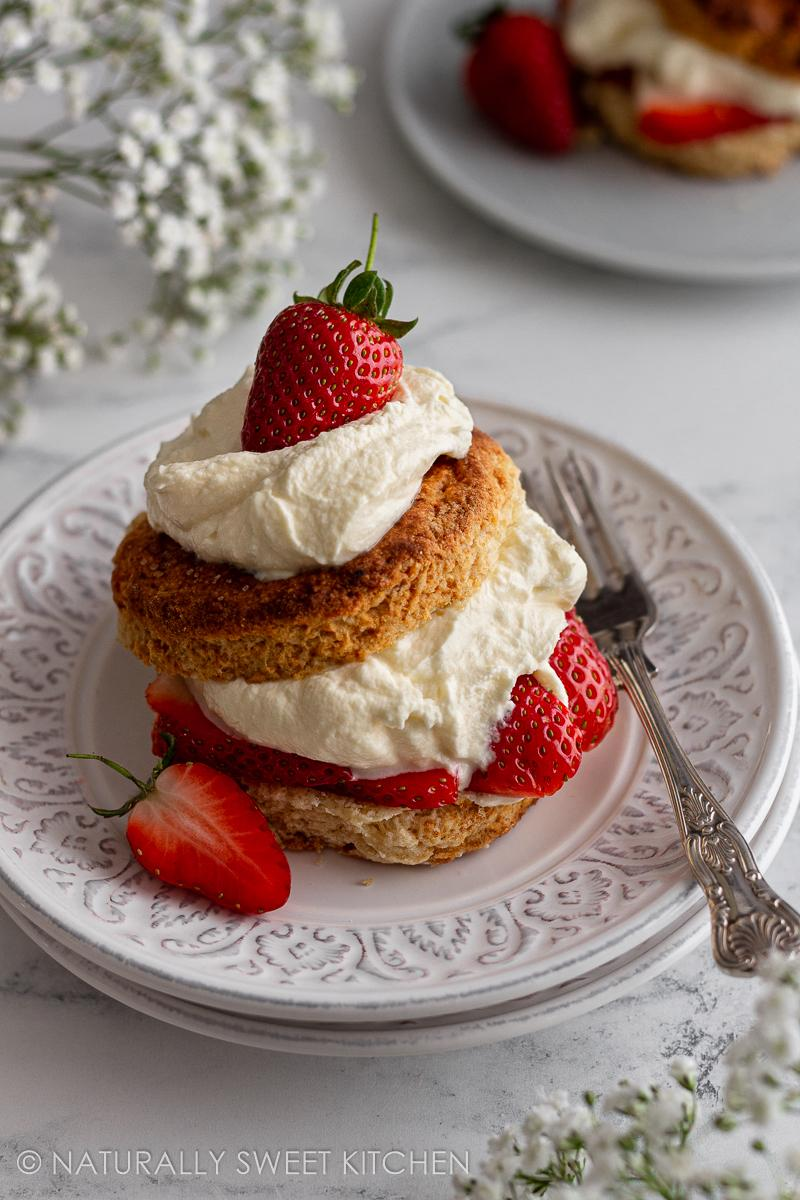 a plate of strawberry shortcake on marble countertop with a fork on the side and white flowers in the background