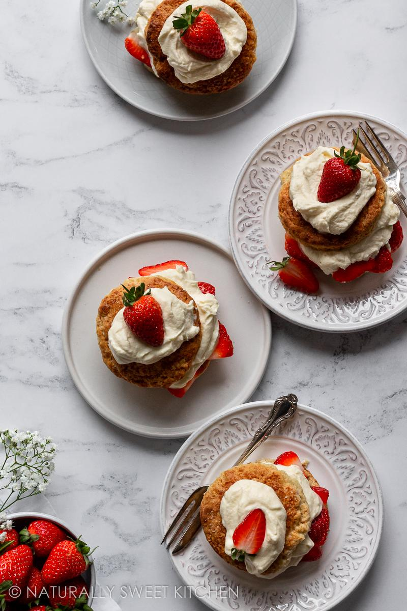 four plates serving strawberry shortcakes topped with whipped cream and a strawberry