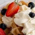a plate of waffles topped with refined sugar free whipped cream, blueberries, and sliced strawberries