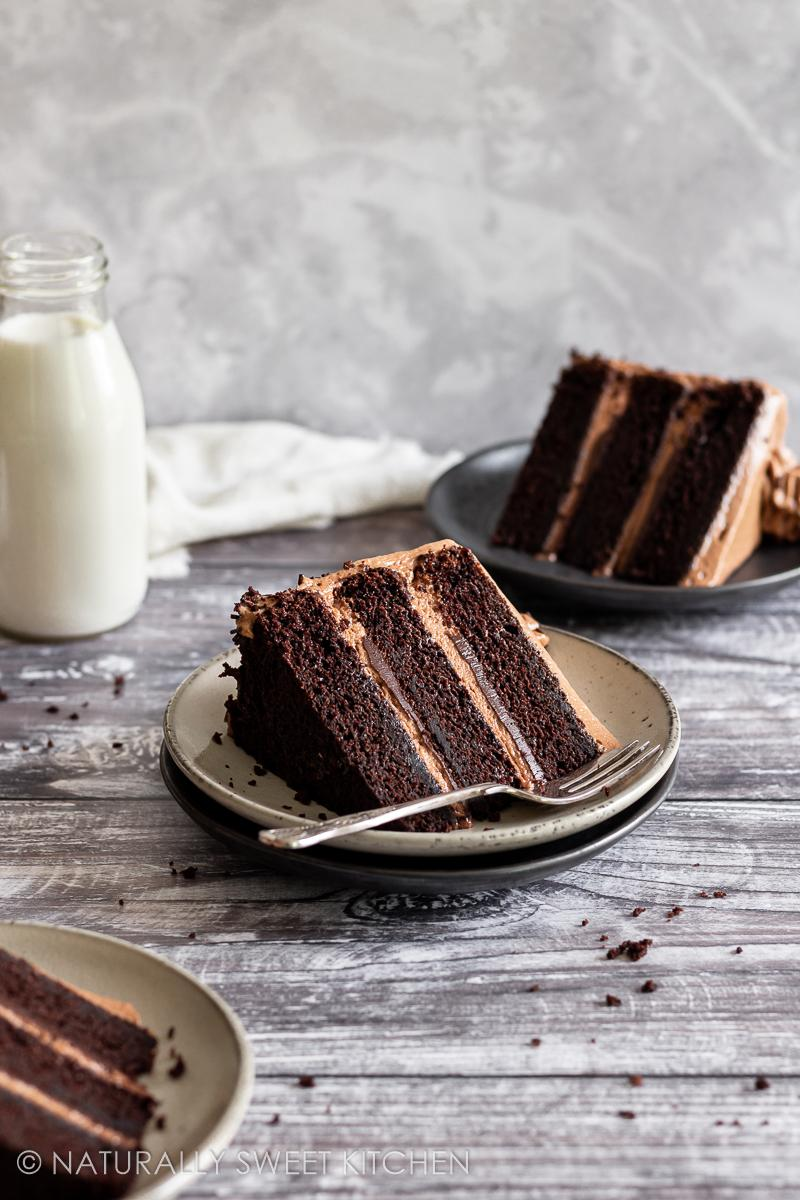 three slices of the best triple chocolate cake recipe on a wooden table with a bottle of milk in the background and crumbs scattered around the table