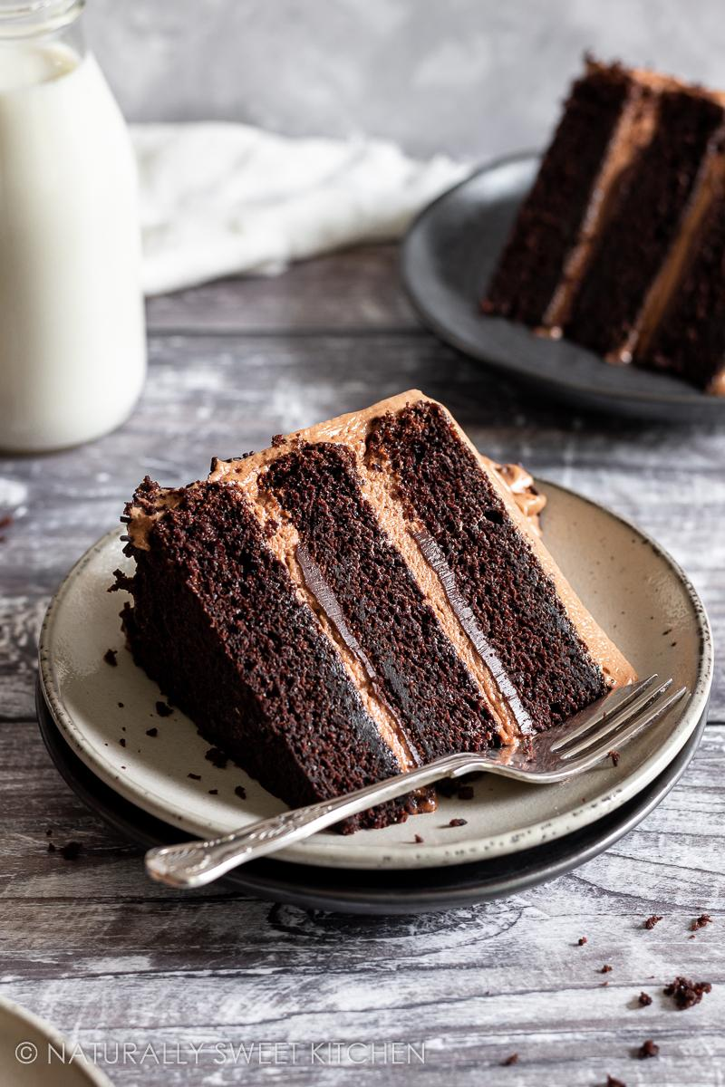 a slice of moist chocolate cake on a beige ceramic plate with a cake fork and crumbs on the table in front of it