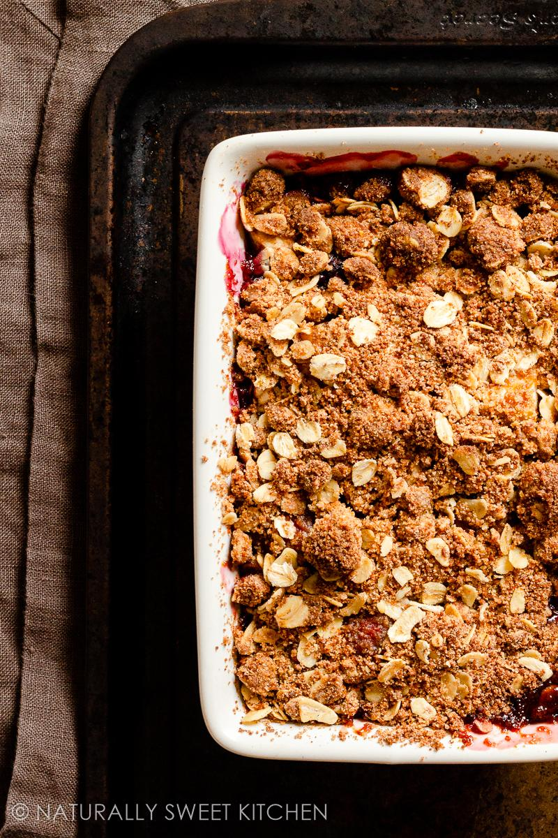 a rectangular serving dish filled with healthy berry crumble on a dark baking tray with a brown linen napkin underneath