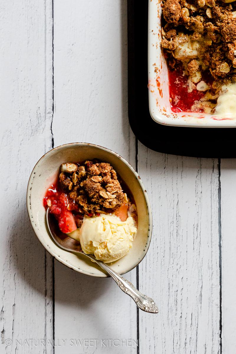 a serving of healthy crumble with apples and berries in a small bowl topped with vanilla ice cream