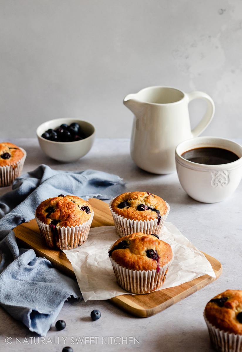 a breakfast scene featuring a batch of fluffy lemon blueberry muffins and a mug of hot coffee