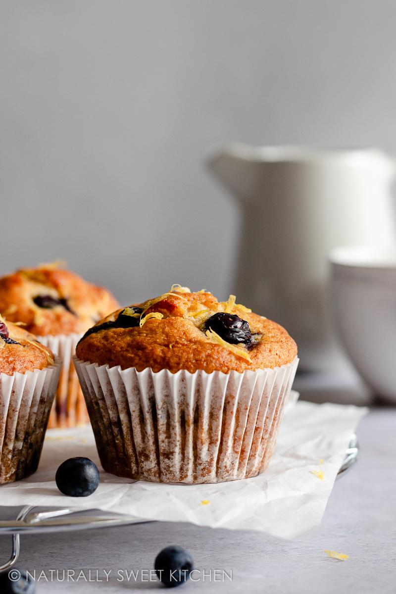 a lemon blueberry muffin is sat on a wire rack and topped with lemon zest; there are blueberries scattered around the countertop
