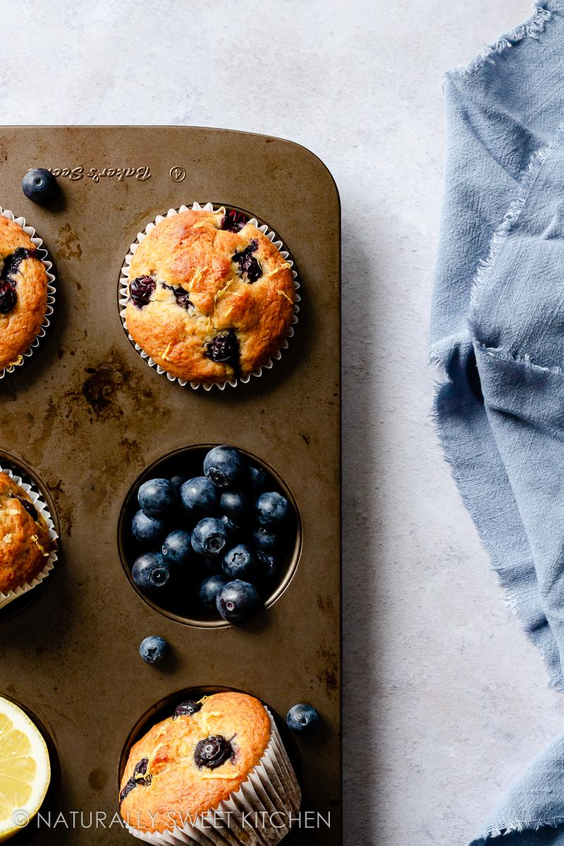 four muffins in a baking tin with one of the tin holes full of blueberries and the other with a half a lemon
