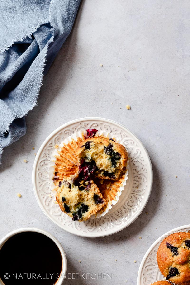 a lemon blueberry muffin on a white plate pulled open to reveal a fluffy interior bursting with blueberries