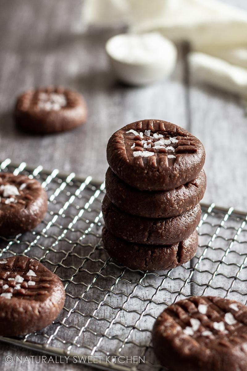 a stack of no-bake chocolate peanut butter cookies on a wire rack topped with sea salt