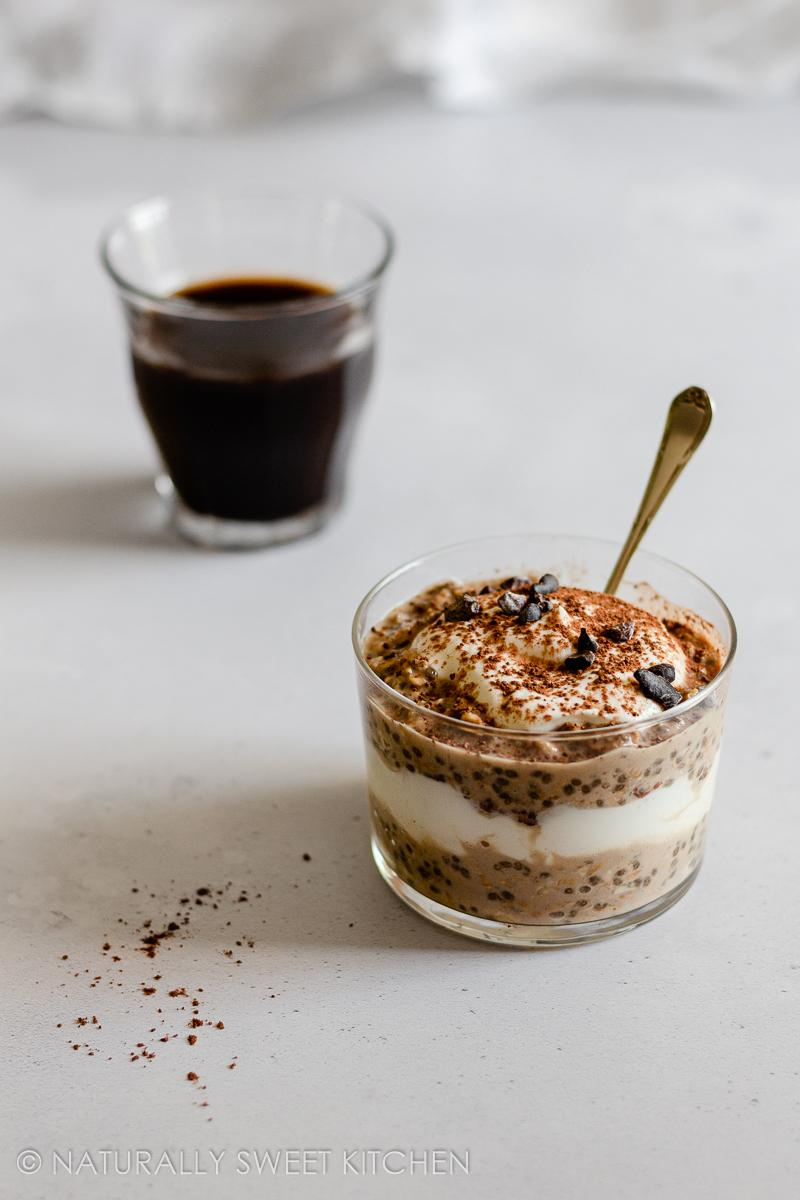 a glass cup filled with layers of coffee overnight oats, yoghurt, and chocolate with a glass of espresso in the background